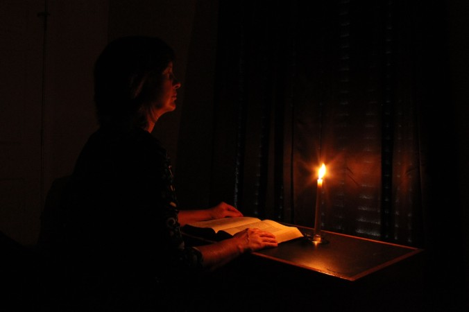 woman sitting in dark with open Bible and single candle burning