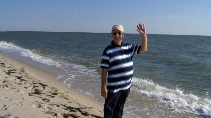 man on the beach waving at the camera