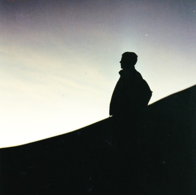 silhouette of man standing on side of mountain at dawn
