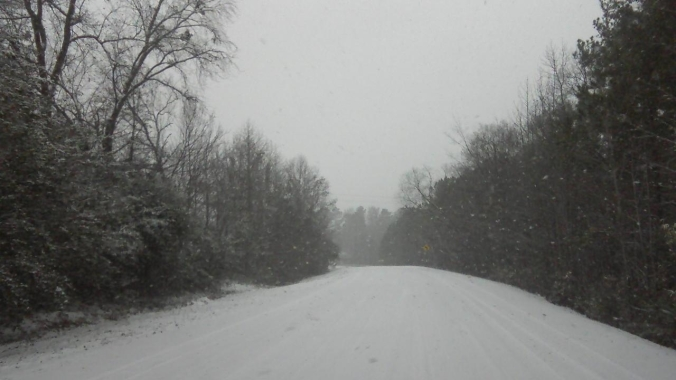 snow falling and blanketing the road
