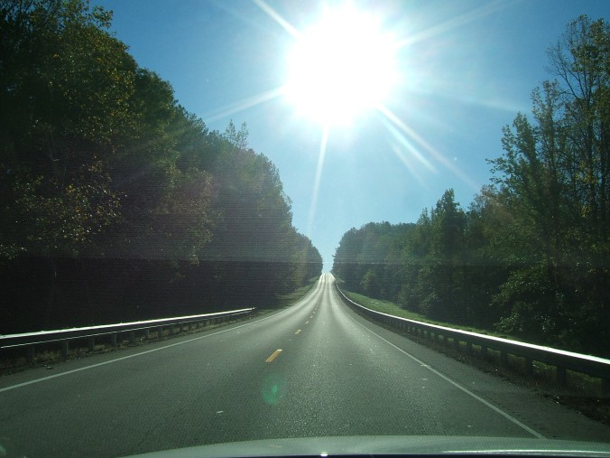 long straight stretch of road with bright sun in view