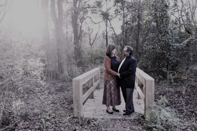 couple standing hand in hand on a bridge